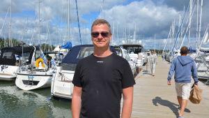 Bent Andersson på en brygga med segelbåtar i bakgrunden.