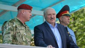 Belarus president Aleksandr Lukasjenko står mellan två militärer och lyssnar på den ena som talar.