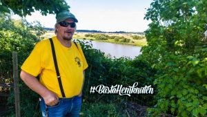 En man i gul t-skjorta och solglasögon står i ett buskage. I bakgrunden en å.