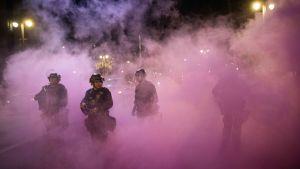 Tre kravallutrustade poliser står i ett moln av tårgas