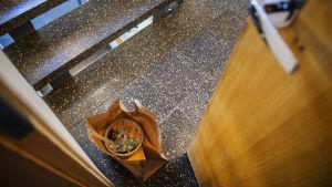 Bilden visar en papperspåse med hämtmat som lämnats framför dörren i ett trapphus.