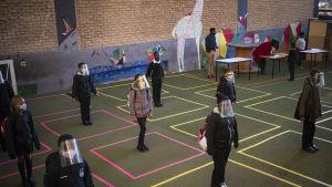 Barn med skyddsvisir står i målade rutor på ett golv