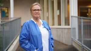 En sjuksötare i vita kläder och knallblå tröja står utanför ingången till jouren vid Raseborgs sjukhus. Höst.