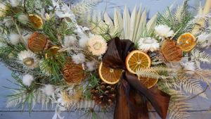 Närbild av en krans med torkade blommor och blad i ljusbeigea färger.