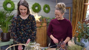 Två kvinnor som står och binder kransar av torkade blommor och växter.