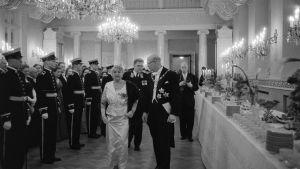Entisen presidentin puoliso Alli Paasikivi ja presidentti Urho Kekkonen itsenäisyyspäivän juhlavastaanotolla Presidentinlinnassa Helsingissä 6.12.1957. Takana Neuvostoliiton suurlähettiläs Viktor Lebedev.