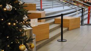Säkerhetsstaket har placerats ut i ett köpcentrum för att förhindra att människor sitter på bänkar i onödan i coronatider.