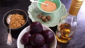 Kokta rödbetor, farinsocker och riven muskot på olika fat på ett bord