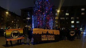 Bild på personer på Tölö torg där personer håller skyltar med antifacistiska budskap.