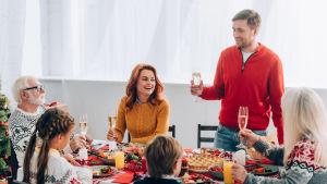 En man står och skålar med skumvin med ett stort sällskap vid bordet.