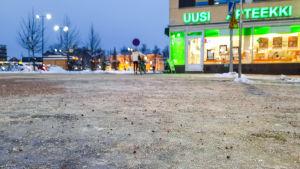 Person med cykel går över gatan i centrum av Borgå. Bilden är tagen nerifrån med fokus på den isiga marken närmast fotografen.