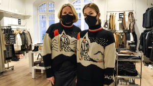 Två kvinnor i likadana stickade tröjor och munskydd står inne i en klädbutik.