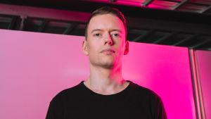 Toimittaja Anton Vanha-Majamaa vaaleanpunaista taustaa vasten.