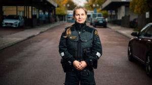 En kvinnlig sjöbevakare står på en gata i Mariehamn. Gamla Zeipels bakgård till vänster i bild.