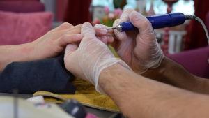 Två händer i engångshandskar håller i en hand utan handske. Naglarna på handen behandlas med en diamantborr.
