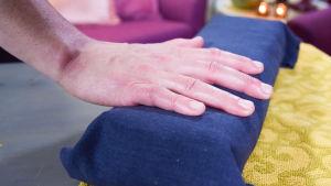 En hand på en blå dyna efter manikyr.