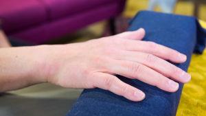 En hand på en blå dyna.
