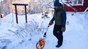 En kvinna som går runt med ett gult mäthjul i en snöklädd trädgård.