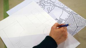 EN hand som håller en penna och ritar upp en skiss av en detaljplan.