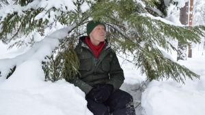 Niklas Aldén sitter under en gran och njuter.