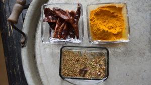 Gurkmeja, torkad chili och kadhai masala i olika skålar på en bricka