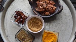 Olika kryddor till indiskgryta på en bricka i ett kök