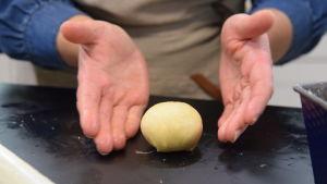 Händer som formar deg till bollar på ett bord