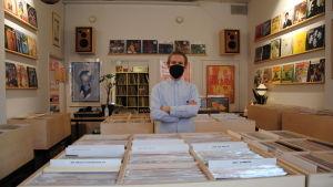 Man med ljusblå skjorta, svar ansiktsmask står med armarna i kors mitt i en vinylaffär.
