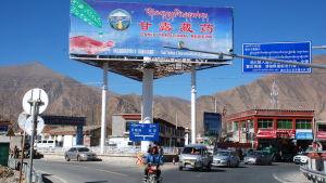 En stor reklamskylt på kinesiska i en vägkorsning