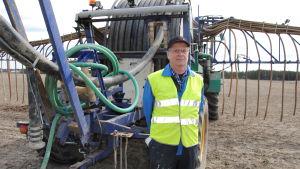 Man med arbetskläder står framför stor traktor på åker.