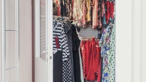 Öppen dörr in till klädaffär med klänningar i vintagestil.