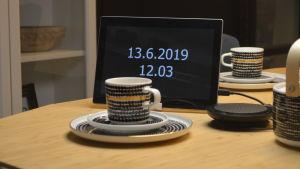 En pekplatta, som står på ett bord med kaffemuggar, via vilken en distansvårdare kan ta kontakt med kunder och diskutera.