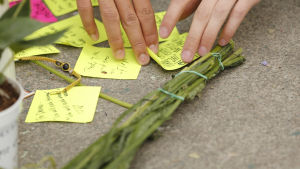Hälsningar till de saknade och döda på små lappar på trottoaren.