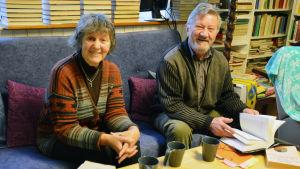 Siv Långstedt och Torsten Bergman sitter i en blå soffa, omringad av böcker. På bordet står böcker och tre kaffekoppar.