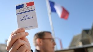Man håller upp sitt röstningskort i kommunen Le Pin i nordvästra Frankrike den 23 april 2017-