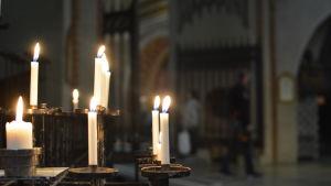 Ljus brinner i ljusstakar i Åbo domkyrka under lördagens kvällsmässa som ordnades för att hedra Åboattackens offer.