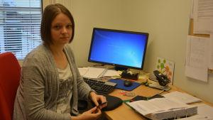 Kvinna sitter i ett arbetsrum med dator i bakgrunden.
