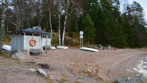 Sandstrand. Roddbåtar ligger upp och ner. Små omklädningsrum.