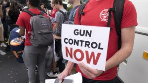 Skolelev håller en skylt med krav på vapenkontroll. Han och andra elever är på väg till delstatens huvudstad Tallahassee för att framföra kravet på ökad vapenkontroll.