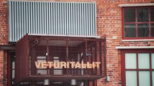 """Ingången till Lokstallet, en skylt som består av en bur där det står """"Lokstallet"""" på finska."""