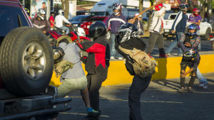 Unga män i motorcykelhjälmar anfaller en demonstrant under protesterna den 18 april i Managua.
