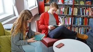 Julia Halttunen och Rasmus Svedberg bläddrar i böcker