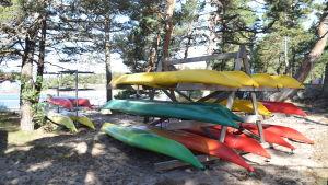 Bilder på kajaker som är uppdragna på stranden. Kajakerna är uppsatta på en ställning av trä. Kajakerna är gula, gröna och röda. I bakgrunden syns havet.