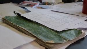 Ett väl använt, slitet häfte och husritningar på ett ett skrivbord.