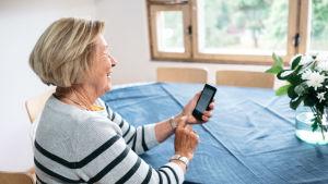 Eläkeikäinen nainen käyttää hymyillen kännykkää kotonaan.