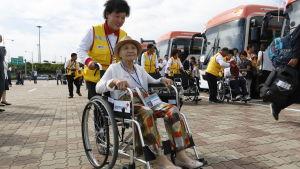 En kvinna som ska delta i familjeåterföreningen i Nordkorea i augusti 2018 får hjälp av en en frivillig från Röda korset.