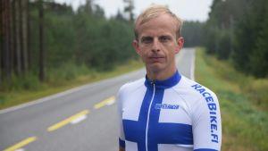 En man står vid en landsväg och tittar in i kameran. Han har en tajt trikåtröja i blått och vitt på sig. Han heter Johan Nordlund.