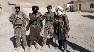 Talibanrebeller med regeringssoldater i Kabul under ett eldupphör i somras