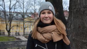 Ida Bengtfolks, en ung kvinna med långt hår iklädd grå mössa och svart rock ser in mot kameran i ett grått Åbo vid aura Å.
