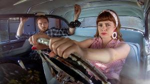 Nainen ajamassa autoa. katsoo kameraan. Pelkääjänpaikalla mies, joka katsoo naista.